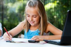 Young girl doing schoolwork with pencil outdoors. Stock Images