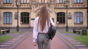 Young girl student is going to university in summer, studying concept, back view.  stock footage