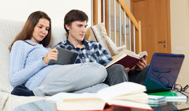 Young girl with student guy learning for examinations together. With laptop in home interior stock photos