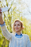 Young girl student having fun and taking selfie photo on smartphone camera outdoor in green park in sunny day, teenage trand. People concept Royalty Free Stock Images