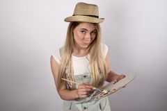 Young girl student with long hair and a scrutiny paints a pictur Stock Images