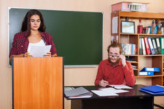Young Girl Student Prepare Report Seminar Standing At Platform In Classroom, Professor Listen High Stock Image