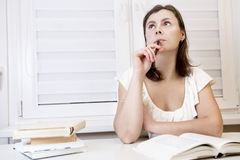 Young girl student preparing for exam with books. woman is studying with textbooks. Preparation for session. Student reads books. girl pondered over material Stock Images