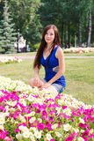 Young girl, student, sits near the flowers in the Park Royalty Free Stock Photo