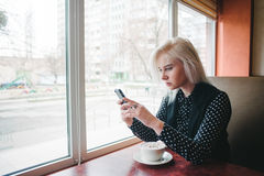 Young girl student sitting in a cozy cafe near the window with a cup of coffee and gaining a message in your phone. Stock Photos