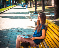 Young girl student sitting on yellow bench Stock Photos