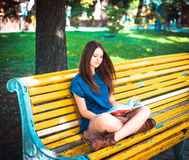 Young girl student sitting on yellow bench Royalty Free Stock Images