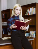 Young girl student standing and reading book near bookshelves in library background Stock Photography