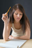 Young girl student sulks. Portrait of a beautiful Isolated  teenager  student. An attractive young student posing at her desk. Picture of a pretty girl isolated Stock Photos