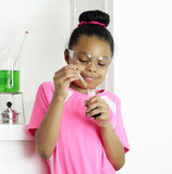 Student samples a prepared mixture. A young girl student uses an eyedropper to sample to sample a prepared solution in chemistry class Stock Image