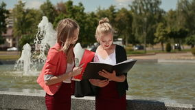 Young girl students of the college together in the park near the fountain. The sun is shining. stock footage