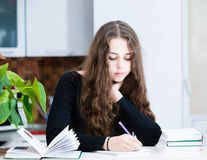 The young girl is studing. In the kitchen Royalty Free Stock Images