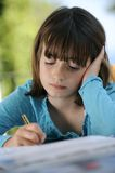 Young girl studying. Young girl (9 years old), writing with pencil Royalty Free Stock Images