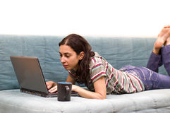 Young girl studying. Young girl typing on her computer laying on the couch Royalty Free Stock Image