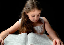 Young Girl Studying Bible. Young girl reading a bible on a small table Stock Photo