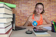 Young Girl studying on desk at home. Books on wooden table Stock Images