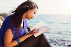 Young Girl Studying Her Bible By The Sea Royalty Free Stock Photos