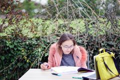 Young girl studying on masters in Clinical Dentistry MClinDent Orthodontics. In the corner of a garden intending to reach her target Royalty Free Stock Image