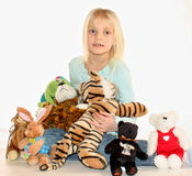 Young girl and stuffed animals. A young girl with all of her stuffed animals royalty free stock images