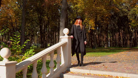 Young girl in stylish coat and hat with wide brim. Charming young girl in stylish coat and hat with wide brim walks in the autumn park stock photo