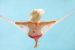 Young girl with a stylish hat lying in a hammock. Rear view studio shot of a young girl with a stylish hat lying in a hammock on blue background royalty free stock photography