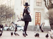 Young girl in a stylish hat, in the street playing with a large number of pigeons. Birds fly up. A young girl in a stylish hat, in the street playing with a royalty free stock photos