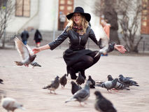 Young girl in a stylish hat, in the street playing with a large number of pigeons. Birds fly up. A young girl in a stylish hat, in the street playing with a royalty free stock photo