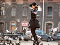 Young girl in a stylish hat, in the street playing with a large number of pigeons. Birds fly up. A young girl in a stylish hat, in the street playing with a stock image