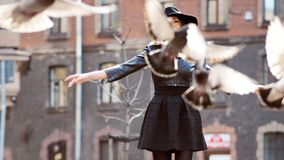 Young girl in a stylish hat, in the street playing with a large number of pigeons. Birds fly up. A young girl in a stylish hat, in the street playing with a stock photo