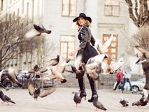 Young girl in a stylish hat, in the street playing with a large number of pigeons. Birds fly up. A young girl in a stylish hat, in the street playing with a royalty free stock photography