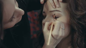 A young girl stylist puts on the eyelids of a brunette model a dark eye shadow. stock video footage