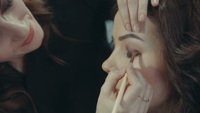 A young girl stylist puts on the eyelids of a brunette model a dark eye shadow. stock video