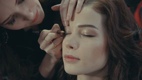 A young girl stylist puts on the eyelids of a brunette model with an eyeliner. stock footage