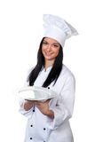 Young girl in a suit holds cooking tray. A young female apprentice chef presents a silver platter Royalty Free Stock Photography