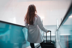 Young girl with suitcase down the escalator. Stock Photo