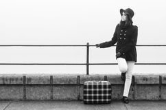 Young girl with suitcase traveling somewhere on misty autumn day Stock Image