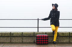 Young girl with suitcase travelling somewhere on misty autumn day Stock Photography