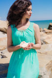 Young girl on summer beach with shell Stock Photo