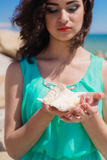 Young girl on summer beach with shell Royalty Free Stock Photos