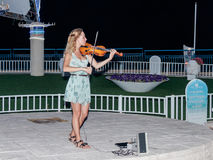 The young girl in the summer evening plays for passers-by on the violin on the waterfront of Nahariya, Israel. Nahariya, Israel, July 26, 2017 : The young girl Royalty Free Stock Photo