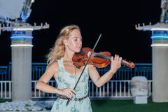 The young girl in the summer evening plays for passers-by on the violin on the waterfront of Nahariya, Israel. Nahariya, Israel, July 26, 2017 : The young girl Royalty Free Stock Images