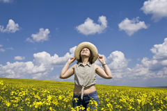 Young girl in summer field. Young attractive woman having fun in rape field Stock Photo