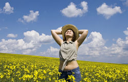 Young girl in summer field. Young attractive woman having fun in rape field Stock Images