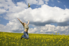 Young girl in summer field. Young attractive girl jumping in rape field and throwing straw hat Stock Photo