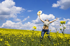 Young girl in summer field. Young attractive girl jumping in spring rape field Stock Photography