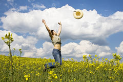 Young girl in summer field. Young attractive girl jumping in spring rape field Royalty Free Stock Image
