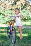 Young girl in summer park on the grass next to bicycle Stock Image