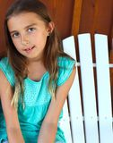 Girl Sits on Edge of Wooden Chair Content and Confident. Young girl in summer teal colored outfit with matching earrings, and long hair combed nicely sits on royalty free stock photos