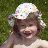 Young girl with sun hat. Young blond girl with sun hat sitting in a meadow Royalty Free Stock Photography