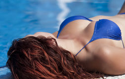 A young girl sunbathing. Girl in blue bikini sunbathing royalty free stock photo